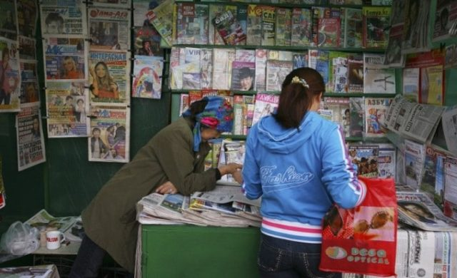 a newstand with a woman and girl minding the stall